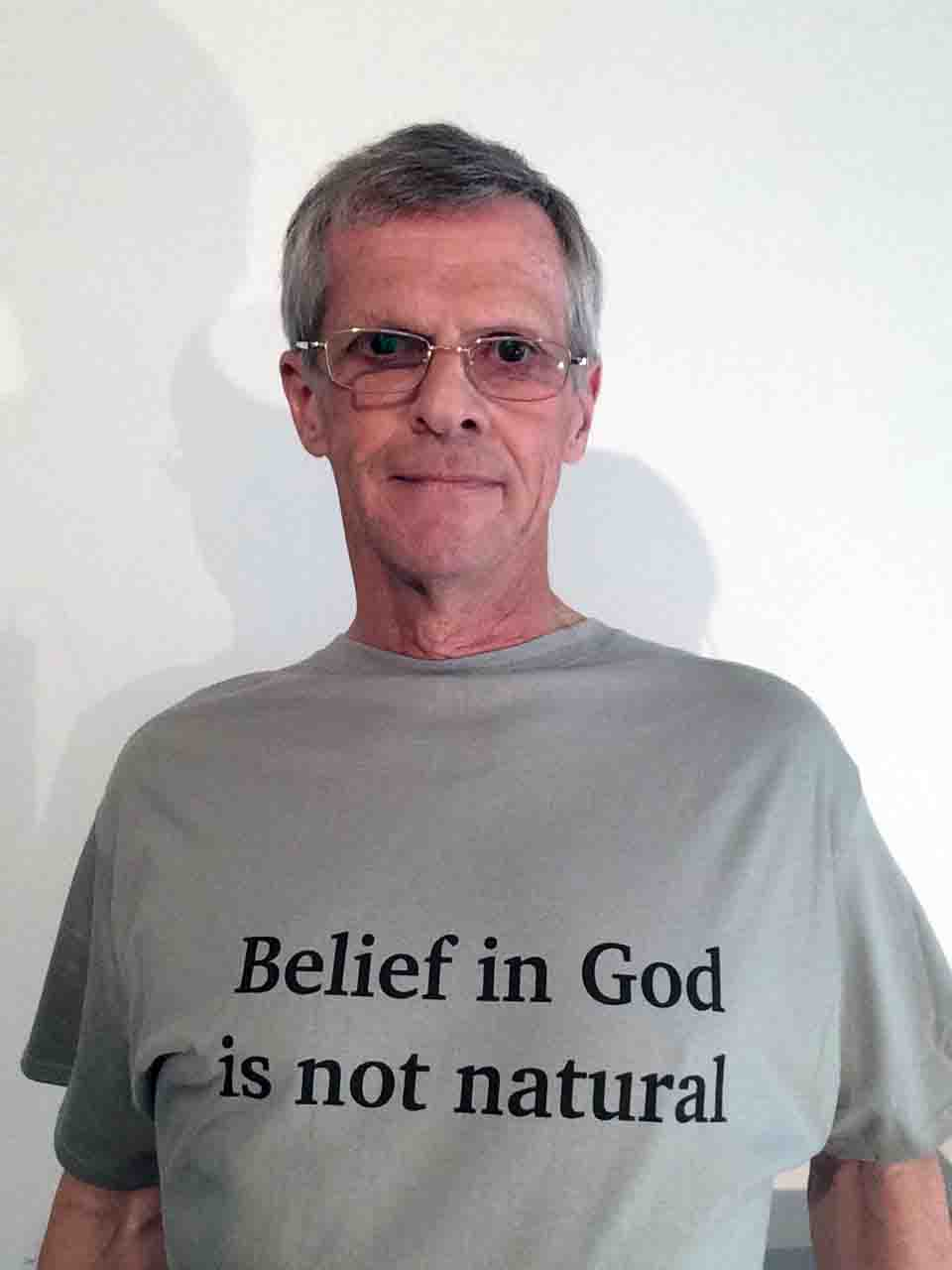 Darwin Bedford wearing a T-shirt simply stating that belief in God is not natural.'