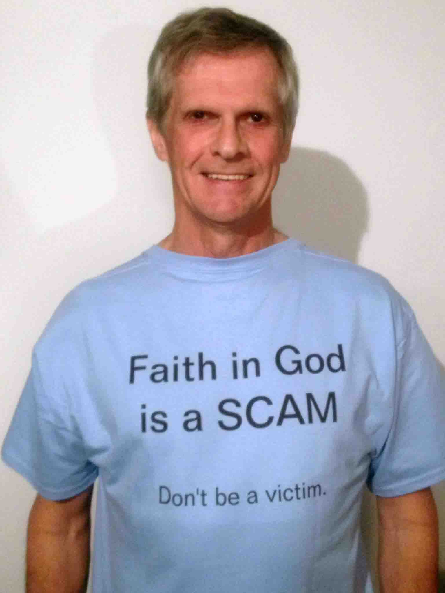 Darwin Bedford wearing his shirt that says 'Faith in God is a Scam -- Don't be a victim'