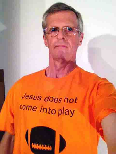 Darwin Bedford wearing his shirt that says 'Jesus does not come into play' and shows a football