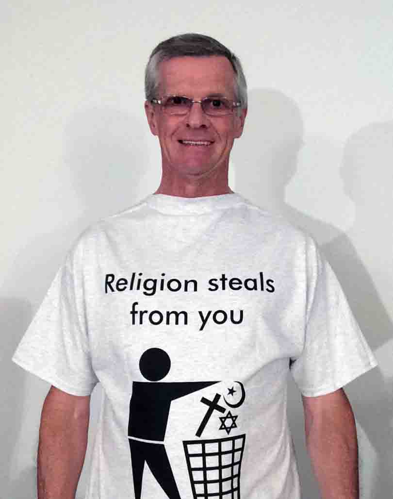 Darwin Bedford wearing his shirt that says 'Religion steals from you with a trash sign'