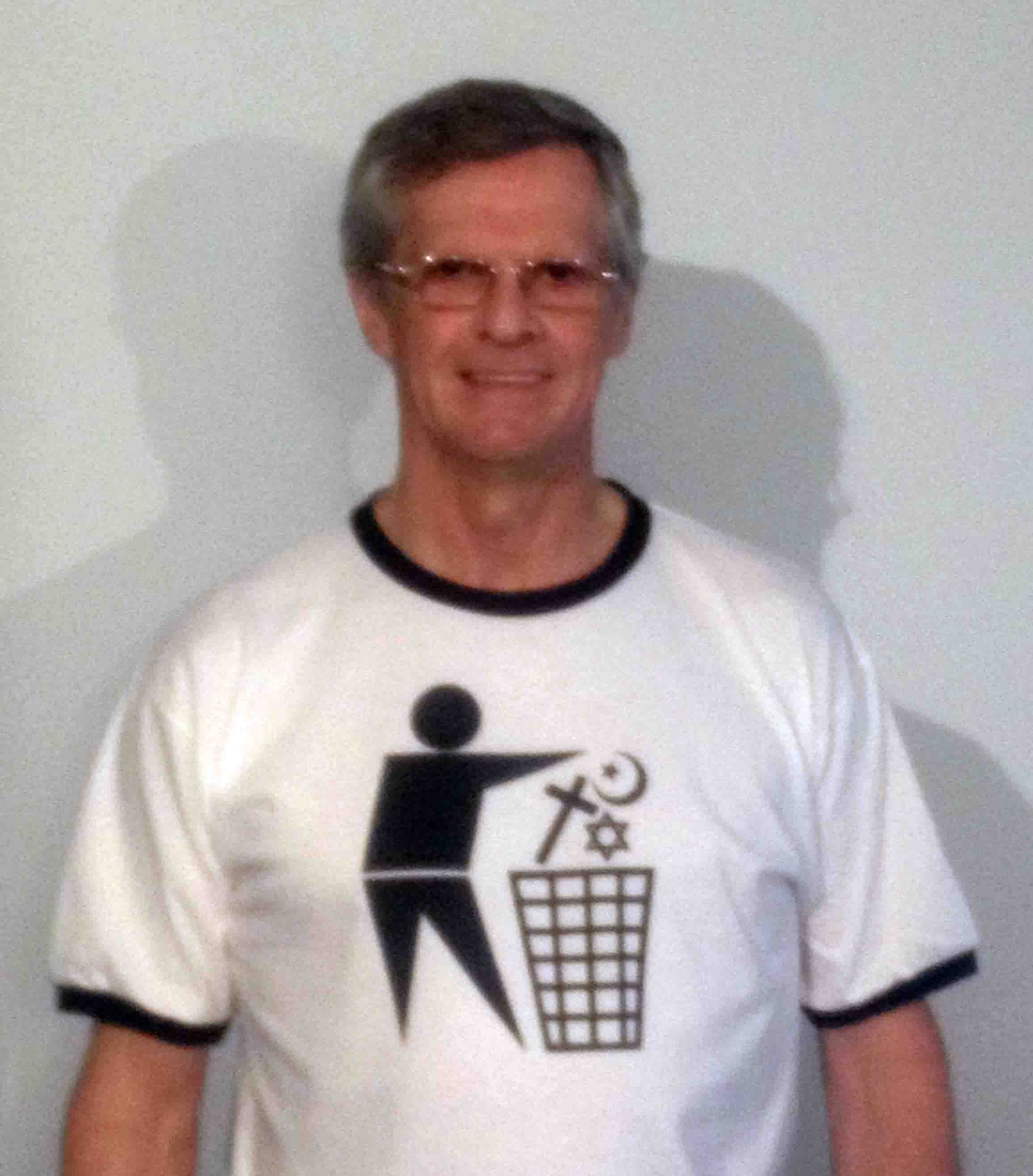 Darwin Bedford wearing a T-shirt depicting the international symbol for a wastes container with religious symbols in place of the wastes.