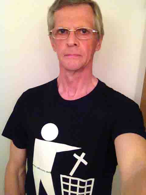 Darwin Bedford wearing a T-shirt depicting the international symbol for a wastes container with a cross in place of the wastes.