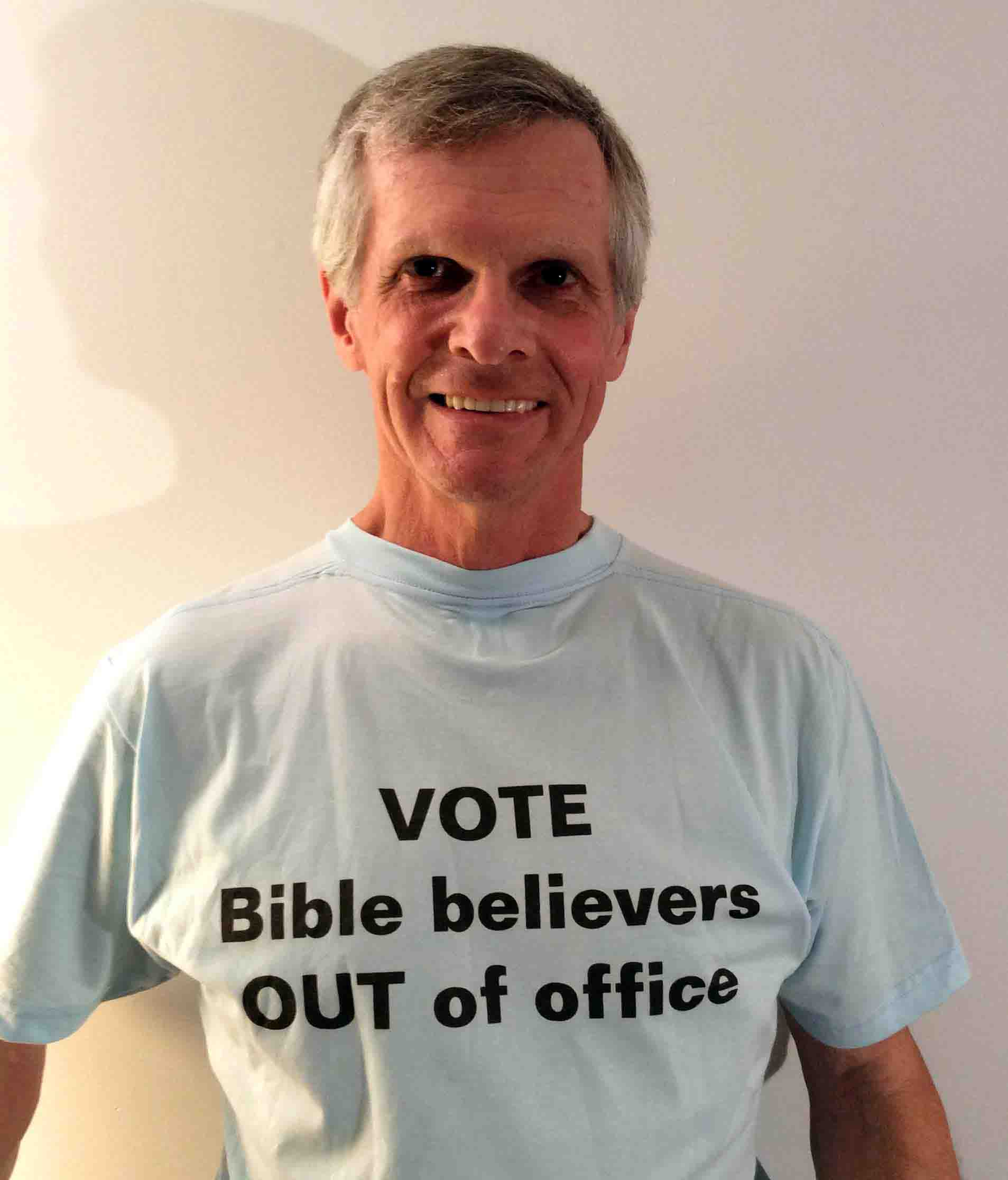 Darwin Bedford wearing his shirt that says 'Vote Bible believers OUT of office'